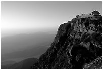 Jinding Si temple perched on a precipituous cliff at sunrise. Emei Shan, Sichuan, China (black and white)