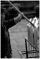 Woman Pilgrim lighting a large incense stick, Wannian Si. Emei Shan, Sichuan, China (black and white)