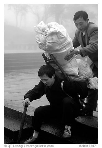 Porter getting helped to shoulder a heavy load on a back frame. Emei Shan, Sichuan, China (black and white)
