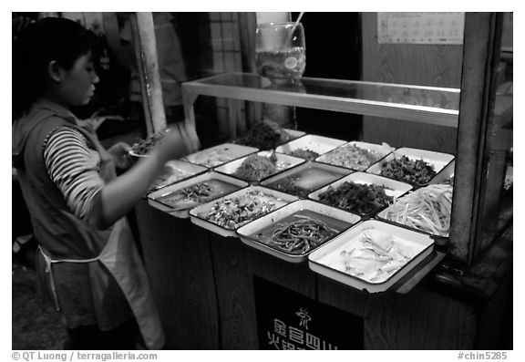 Woman helping herself to food. Sichuan food is among China's spiciest. Chengdu, Sichuan, China (black and white)