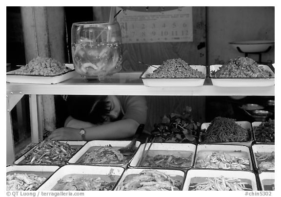 Vendor taking a nap at a food stall.. Chengdu, Sichuan, China