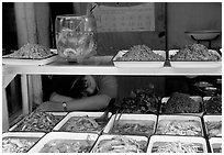 Vendor taking a nap at a food stall.. Chengdu, Sichuan, China ( black and white)