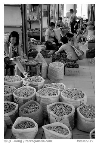 Woman selling dried food items inside the Qingping market. Guangzhou, Guangdong, China (black and white)