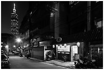 Dark street, store with lanters, and Taipei 101. Taipei, Taiwan (black and white)