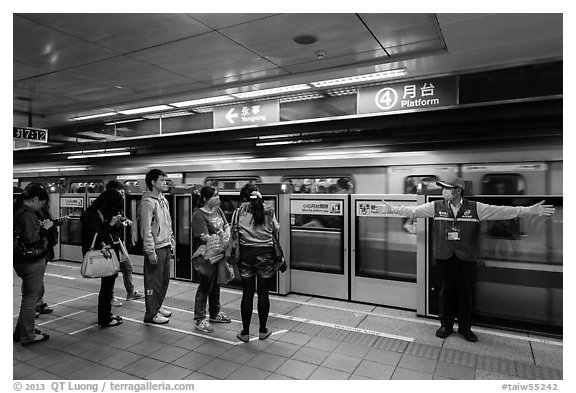 Subway with staff directing passengers. Taipei, Taiwan (black and white)