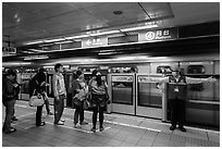 Subway with staff directing passengers. Taipei, Taiwan ( black and white)
