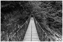 Hiker on suspension footbridge, Taroko Gorge. Taroko National Park, Taiwan (black and white)