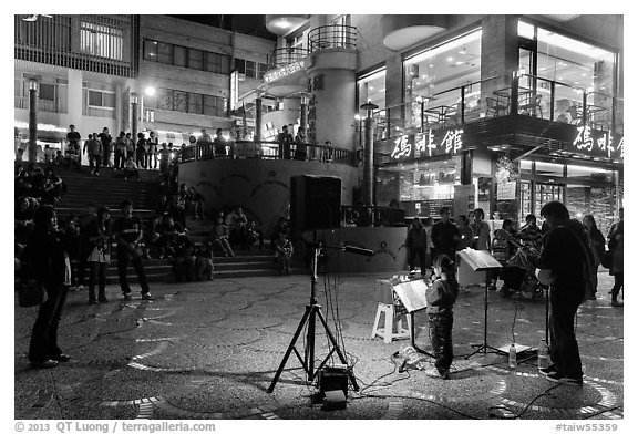 Tourists watch girl singing at night near the pier, Shueishe Village. Sun Moon Lake, Taiwan (black and white)