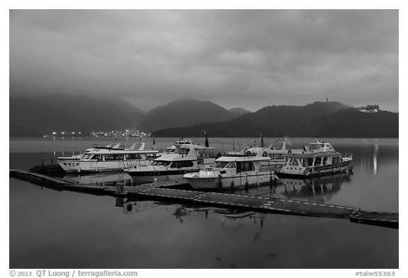 Pier with distant lights of Itashao Village and Syuanzang Temple at dawn. Sun Moon Lake, Taiwan (black and white)