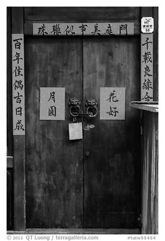 Wooden door traditional lock and chinese inscription on red paper. Lukang, Taiwan (black and white)