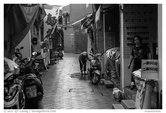 Woman cleaning in alley. Lukang, Taiwan (black and white)