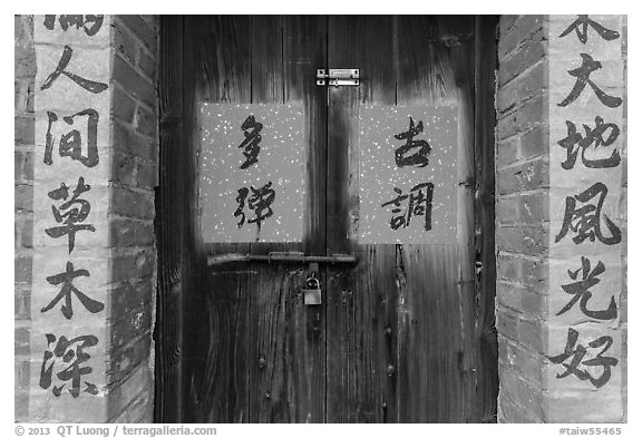 Wooden door and brick wall with Chinese writing. Lukang, Taiwan (black and white)