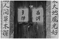 Wooden door and brick wall with Chinese writing. Lukang, Taiwan ( black and white)