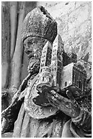 Statue outside of Notre Dame Cathedral showing a model of the cathedral being held. Tournai, Belgium (black and white)
