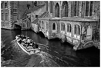 Tour boat goes by a church on a canal. Bruges, Belgium (black and white)
