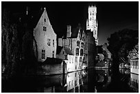 Old houses and beffroi reflected in canal at night. Bruges, Belgium (black and white)