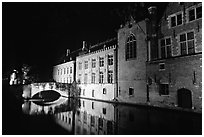 Bridge and houses reflected in canal at night. Bruges, Belgium (black and white)