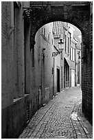 Narrow cobled street and archway. Bruges, Belgium (black and white)