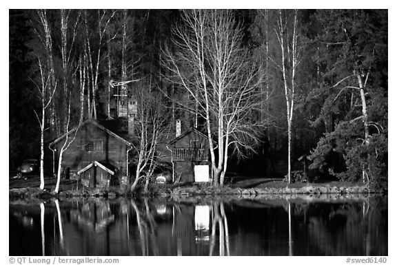 Black and white picture photo wooden house reflected in a lake at sunset central sweden
