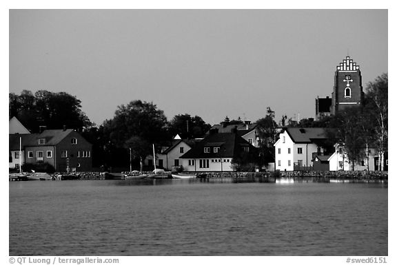 Houses, church, across the lake at dusk, Vadstena. Gotaland, Sweden (black and white)
