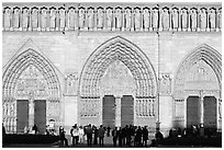 People standing in front of gates of Notre Dame Cathedral, late afternoon. Paris, France (black and white)