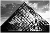 Sunset and clouds seen through Pyramid, the Louvre. Paris, France (black and white)