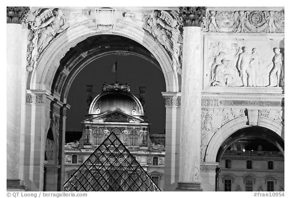 Louvre and  pyramid  seen through the Carousel triumphal arch at night. Paris, France (black and white)
