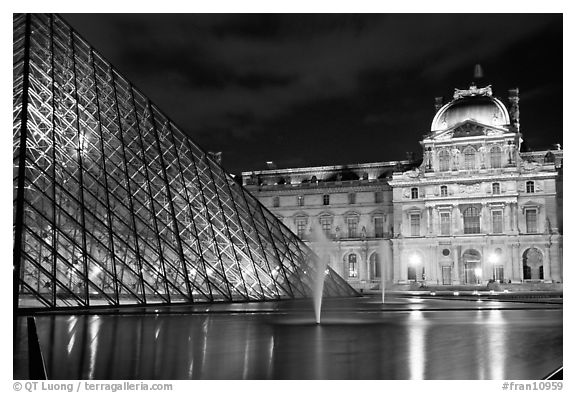 Pyramid, basin, and Louvre at night. Paris, France (black and white)