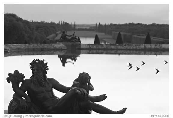 Sculptures, basin, and gardens at dusk, Palais de Versailles. France (black and white)