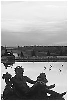 Sculptures, basin, and gardens at dusk, Versailles Palace. France (black and white)