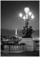 Bronze lamp post with scultpure on Pont Alexandre III, and Eiffel Tower at night. Paris, France (black and white)