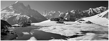 High mountain landscape with partly frozen lake and Mont-Blanc Range. France (Panoramic black and white)