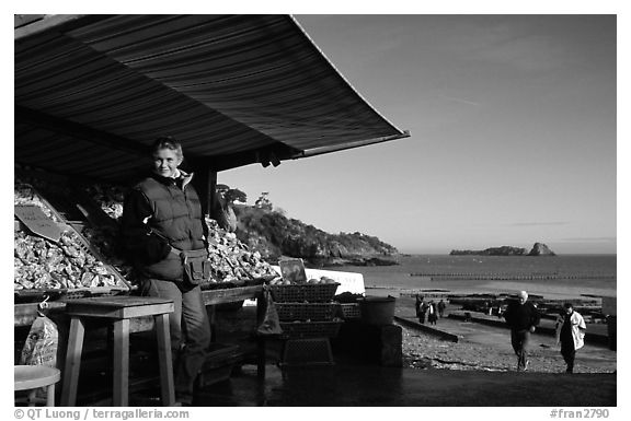 Oyster stand and vendor in Cancale. Cancale oysters are reknown in France. Brittany, France (black and white)