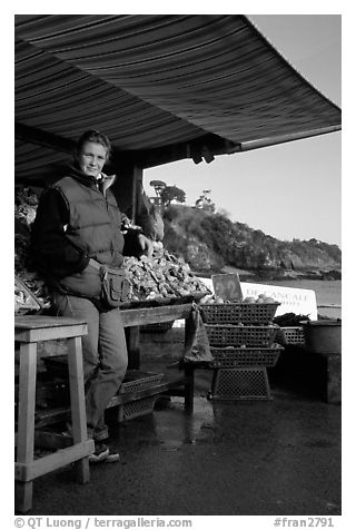 Oyster stand and vendor in Cancale. Brittany, France (black and white)