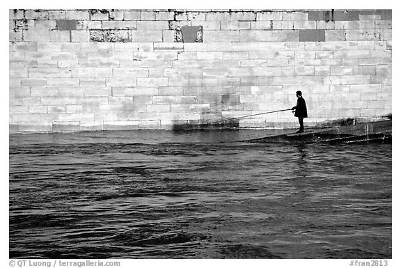Man standing at water level fishing in the Seine River. Paris, France (black and white)
