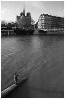 Fishing in the Seine river, Notre Dame Cathedral in the background. Paris, France ( black and white)
