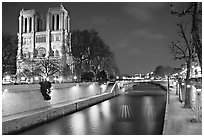 Facade of Notre Dame and Seine river at night. Paris, France ( black and white)