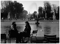 Couple sitting by basin in Tuileries Gardens. Paris, France ( black and white)