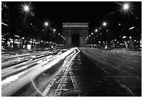 Arc de Triomphe seen from the middle of Champs Elysees at night. Paris, France (black and white)