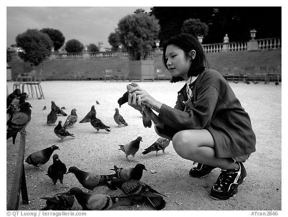 Girl feeding pigeon, Jardin du Luxembourg. Quartier Latin, Paris, France (black and white)