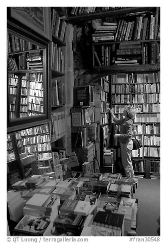 Picking-up a book in Shakespeare and Co bookstore. Quartier Latin, Paris, France (black and white)