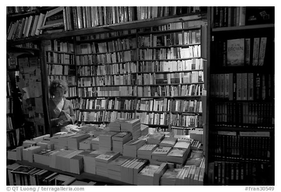 Black and white picture photo checking a book in shakespeare and company bookstore quartier latin paris france