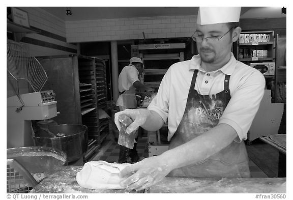 Baker preparing a loaf of break. Paris, France (black and white)