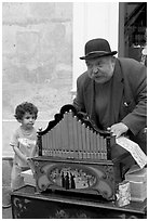 Barrel organ player and kid. Quartier Latin, Paris, France (black and white)