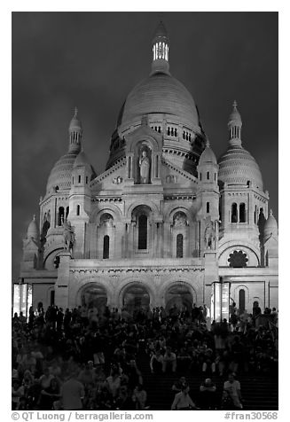 Visitors sitting on the stairs of the Sacre coeur basilic in Montmartre at night. Paris, France