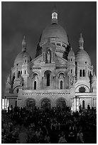Tourists sitting on the stairs of the Sacre coeur basilic in Montmartre at night. Paris, France (black and white)