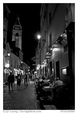 Dinners and narrow pedestrian street at night, Montmartre. Paris, France (black and white)