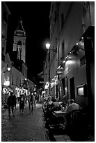 Dinners and narrow pedestrian street at night, Montmartre. Paris, France ( black and white)