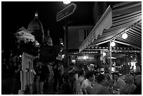 Outdoor dining at night on the Place du Tertre, Montmartre. Paris, France (black and white)