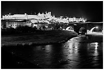 Fortified city and Pont Vieux crossing the Aude River by night. Carcassonne, France (black and white)